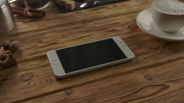 Az okostelefon vízszintes pozíciója a fa asztalon a kávécsésze közelében a fa asztalon
