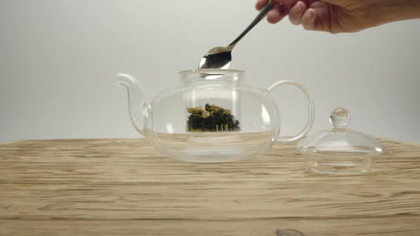 Dry white tea in transparent teapot, males hand covers the pot with a lid