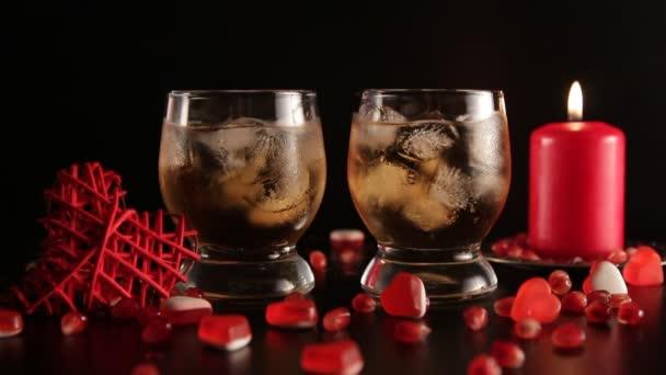 Konfety, padají zpomaleně. Dvě skleničky s alkoholem zdobené bonbóny, červenou svíčku, closeup. Romantické zátiší izolované na černém pozadí. Svatý Valentýn oslava. Dlouhé shot