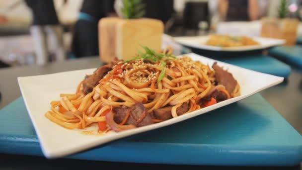 Vařené špagety carbonara v talíř na stůl, zblízka. Zoom fotoaparátu. Tradiční jídlo. Nudle s masem a zeleninou. Street food festivalu