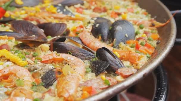 Španělská paella s žlutá rýže, krevety a slávky vaření na trhu s potravinami. Street food festivalu. Rýže s mořskými plody varu zblízka. Tradiční španělská jídla