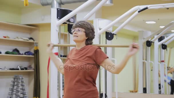 Elderly woman turning with stick, doing physiotherapy exercises in fitness room. Healthy gymnastics. Active seniors.