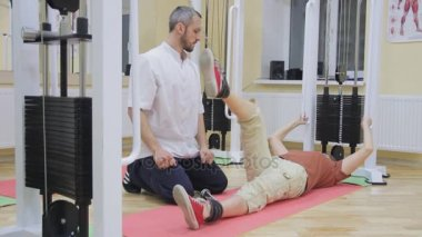 Physiotherapist helping elderly woman lifting legs, doing exercises in fitness room. Healthy gymnastics. Active people.