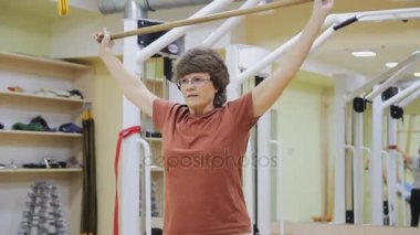Elderly woman lifting stick, doing physiotherapy exercises with in fitness room. Healthy gymnastics. Active seniors.