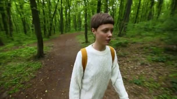Traveler girl with backpack walking in the forest. Travel concept.