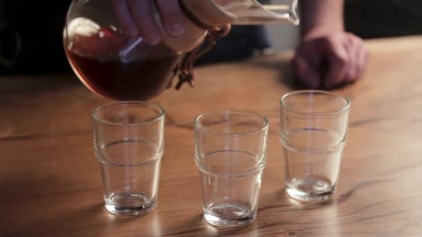 Teát vagy kávét töltök csészékbe. Barista kávét készít közelről..