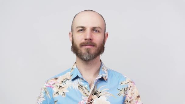 Egy nyugodt, szakállas férfi portréja, aki hawaii inget visel, fehér háttérrel. Az érzelmek fogalma.