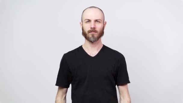 Portrét klidného vousatého muže, hledícího na kameru izolovanou přes bílé pozadí. Nehybné pózování.