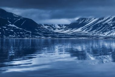 landscape of the Arctic Ocean and reflection with blue sky and winter mountains  Norway, Spitsbergen, Longyearbyen, Svalbard
