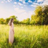 Fotografie nádherný atraktivní dáma mladá štíhlá brunetka s dlouhé šaty procházel zelený park s květinami na západu slunce životní styl