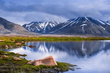 landscape of the Arctic Ocean and reflection with blue sky and mountains with snow on a sunny day, Norway, Spitsbergen, Longyearbyen, Svalbard, summer,