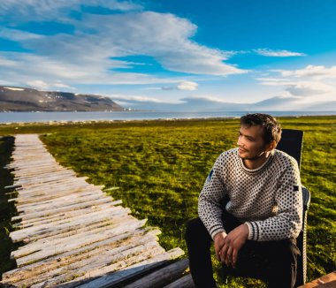 Portrait norway landscape nature of the mountains of Spitsbergen Longyearbyen Svalbard man  in sweater with beard smiling lyifestyle on a polar day  arctic summer in the sunset and blue cloudly sky