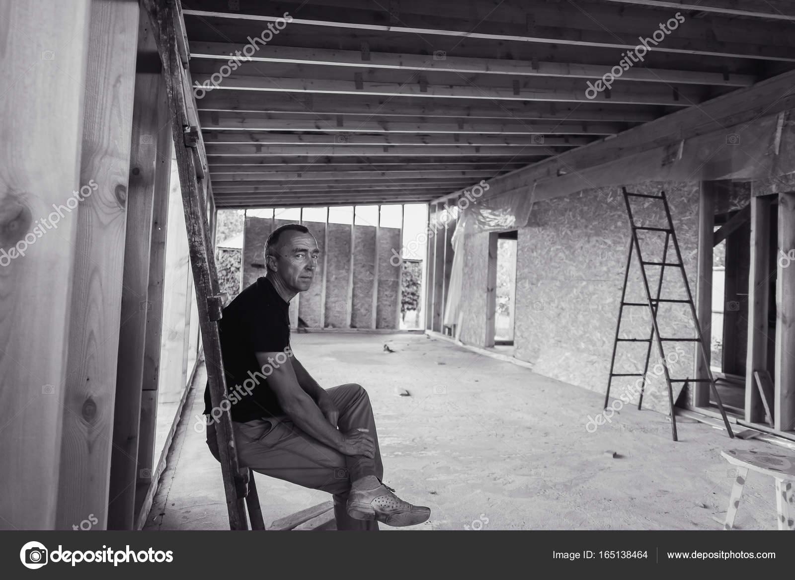 Construcción y hombre de la casa marco edificio nuevo están ...