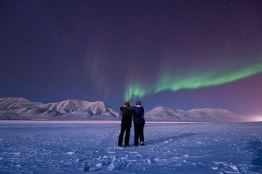 The polar arctic Northern lights aurora borealis sky star in Norway Svalbard in Longyearbyen city man people mountains