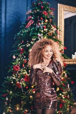 portrait of beautiful young  curly girl on background merry Christmas happy new year tree lights with star disco decor