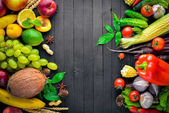 Large selection of raw vegetables and fruits on a black wooden table. Free space for your text. Top view.