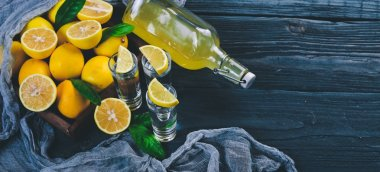 Tequila, fresh lemon and lemon juice. On a wooden background. Top view. Free space for your text.