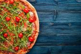 Pizza Primavera. Cherry rajčata, rukola, sýr. Na dřevěné pozadí. Pohled shora.