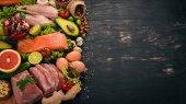 Zdravé potraviny na pozadí. Koncept zdravých potravin, kuřecí řízek, syrové maso, ryby, avokádo, brokolice, čerstvá zelenina, ořechy a ovoce. Na dřevěné pozadí. Pohled shora. Kopírovat prostor.