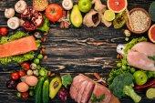 Fotografie Zdravé potraviny na pozadí. Koncept zdravých potravin, kuřecí řízek, syrové maso, ryby, avokádo, brokolice, čerstvá zelenina, ořechy a ovoce. Na dřevěné pozadí. Pohled shora. Kopírovat prostor.