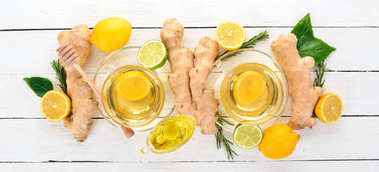 Tea with mint, ginger and lemon. Hot drink On a wooden background. Top view. Copy space.