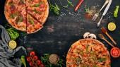 Pizza s kuřecím masem a žampiony. Pohled shora. Na dřevěné pozadí. Kopírovat prostor.