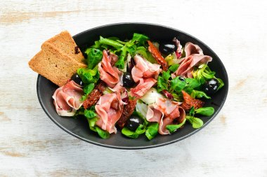 Prosciutto salad with olives in a black bowl. Spanish cuisine. Top view. Free space for your text. Rustic style.