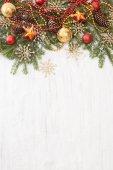Smrkové větve s vánoční ozdoby na bílém pozadí dřevěná