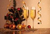 Sklenice šampaňského na vánoční pozadí s létáním sníh