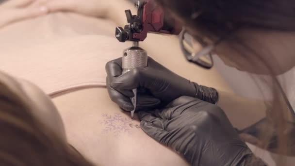 A fekete kesztyűs mester egy tetovált hópelyhet készít egy lánynak a vállán.