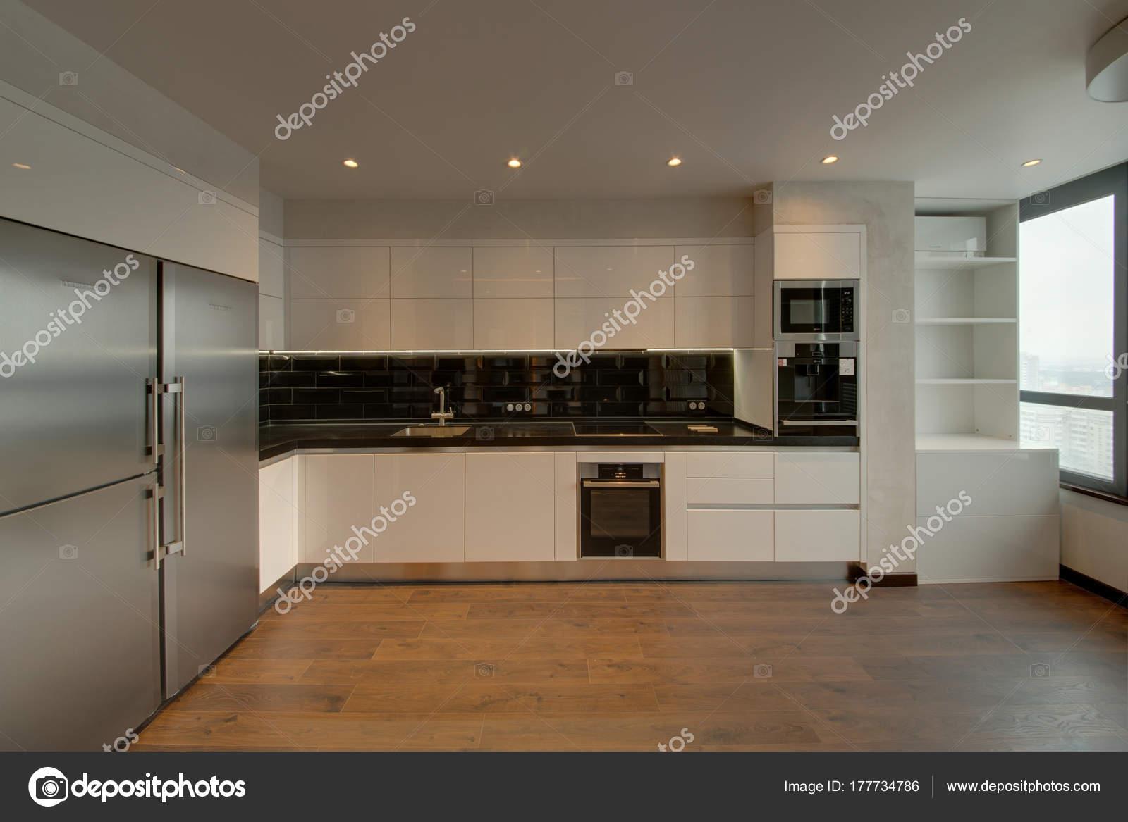 Witte keuken met een zwarte schort een houten vloer u stockfoto