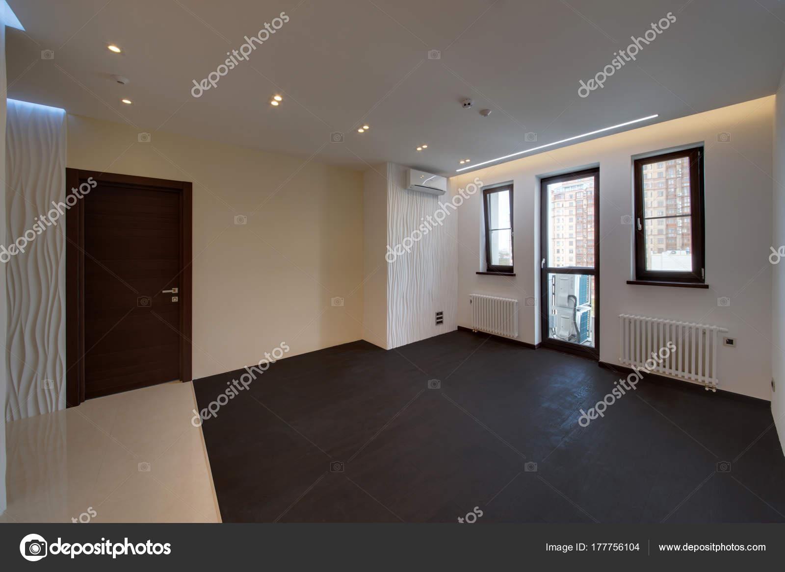 Een salon met een zwarte houten vloer grote ramen een u stockfoto