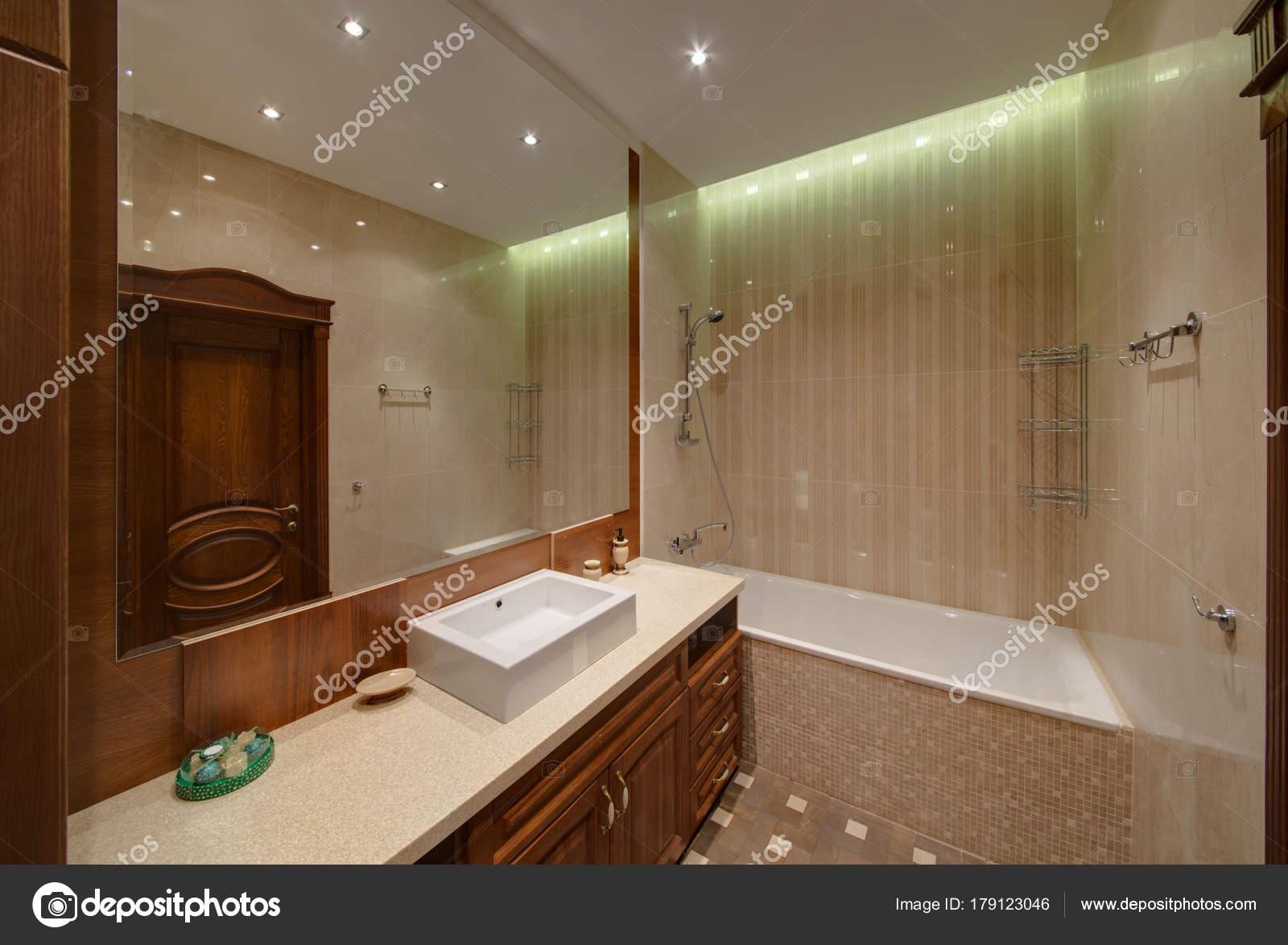 Bagno con mobili scuri sotto lavandino grande specchio una doccia