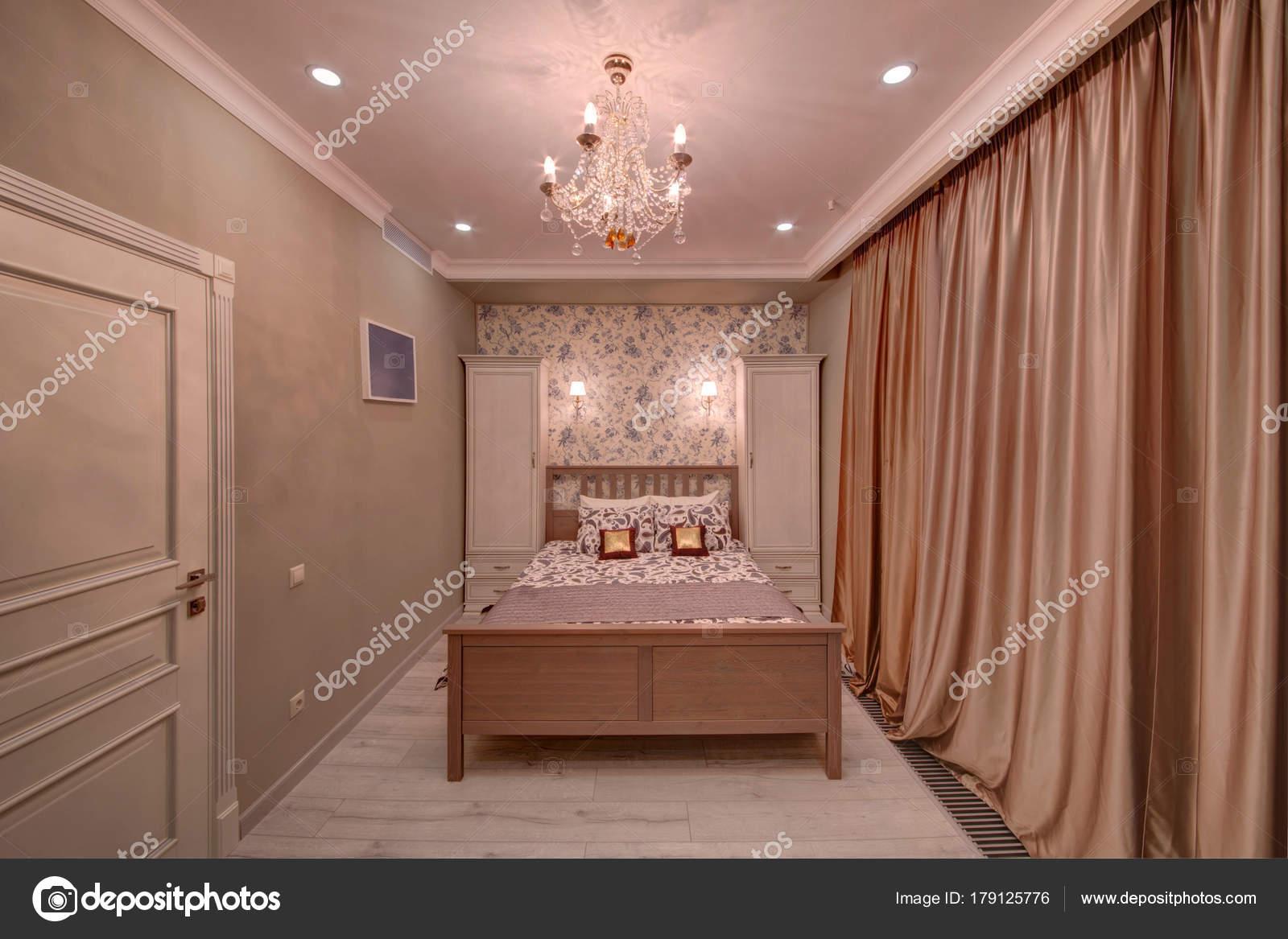 Camera letto con letto crema tende due casi lampadario cristallo