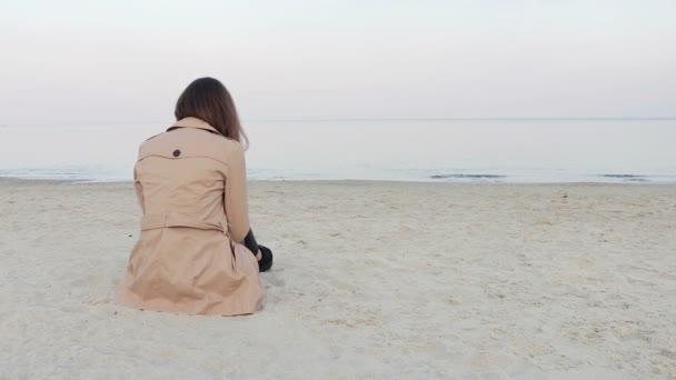 Woman in beige coat sitting on the beach