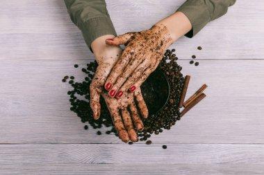 Female hands rubbing the coffee scrub closeup