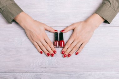 Red nail polish and female hands with manicure