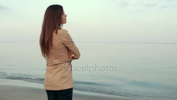 Young slender brunette in a beige coat standing on the beach