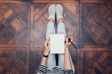 Girl in jeans sitting on the floor at home and writing in a note
