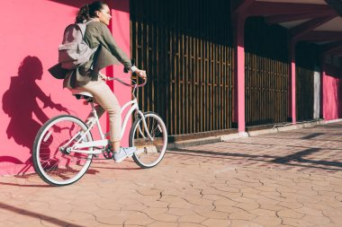 Smiling girl on a Bicycle rides along a pink wall