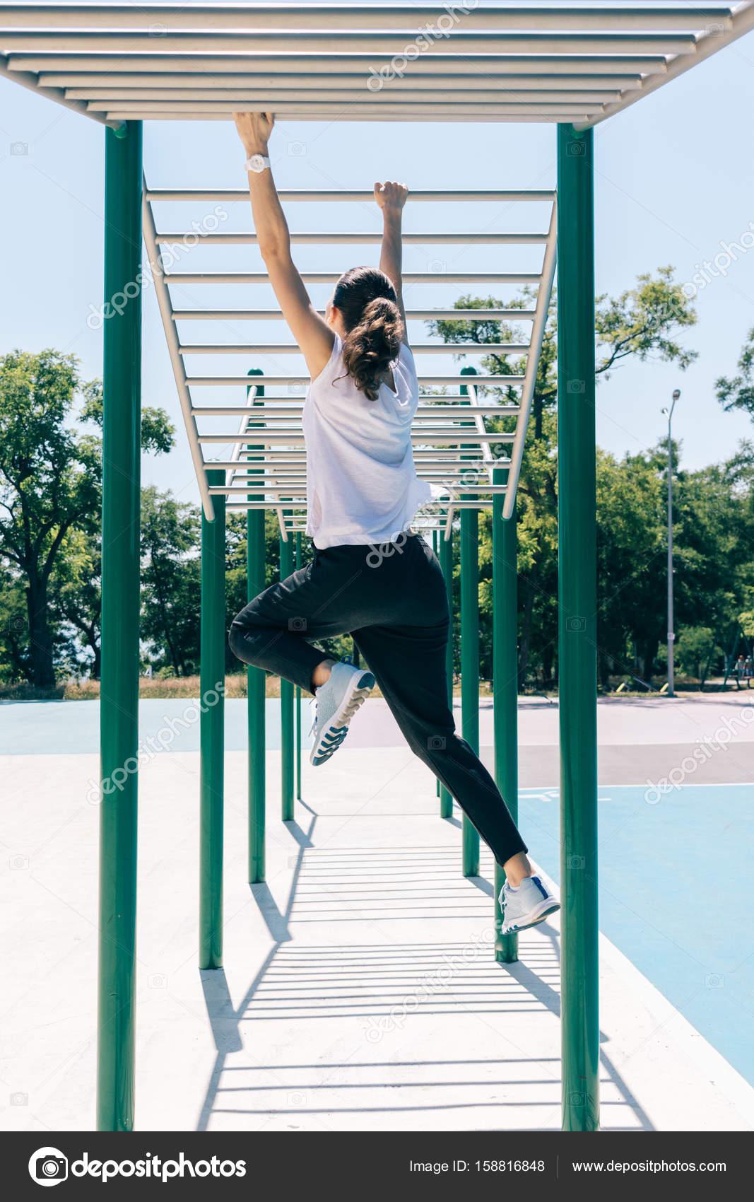 Joven atlética haciendo ejercicios en un campo de deportes en verano ...