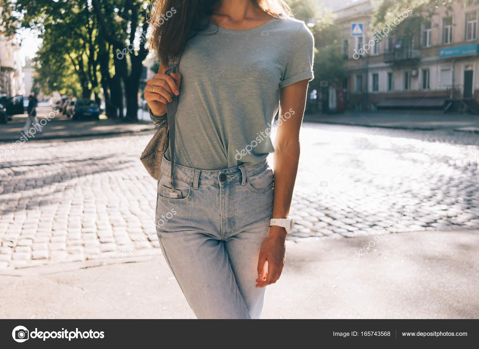 49bac938a2c1 Slim κορίτσι με τζιν και μπλουζάκια με το υπόβαθρο της πόλης το καλοκαίρι —  Εικόνα από ...