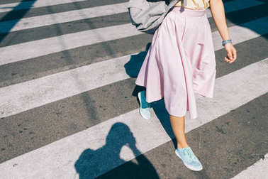 Young woman in a pink skirt and sneakers