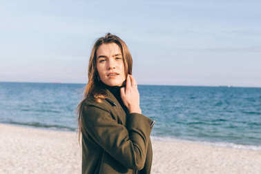 Beautiful brunette in a green coat on the beach