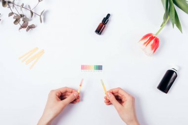 Woman check cosmetics pH level by using litmus paper