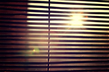 glare from bright sunlight through the wooden Rom Blinds