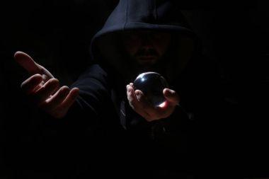 adam siyah başlıklı cristal topu ile