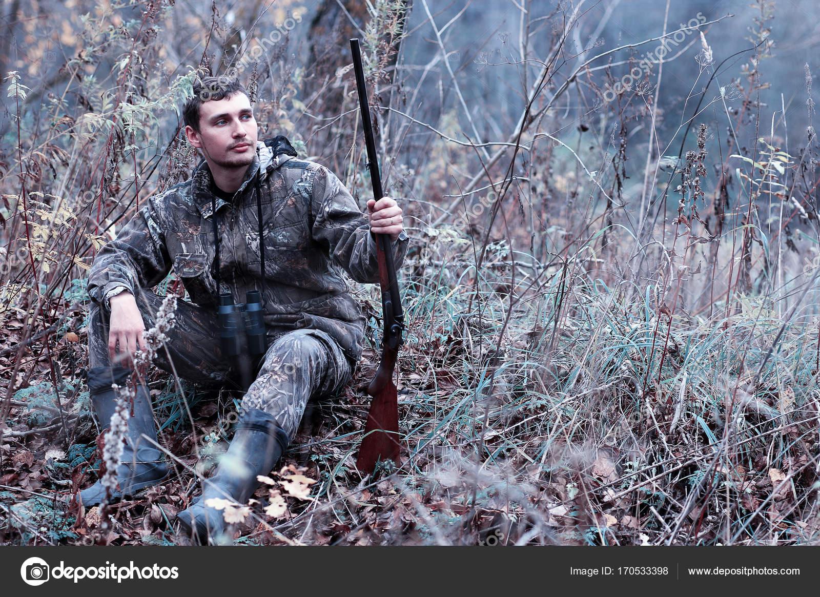 un homme en tenue de camouflage et avec un fusil de chasse dans une for t sur un sp. Black Bedroom Furniture Sets. Home Design Ideas