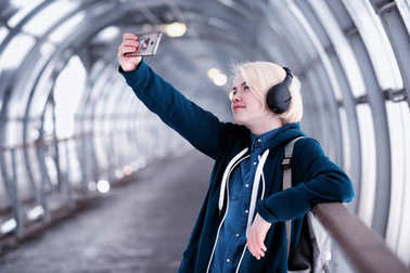 Young student listening to music in big headphones in the subway