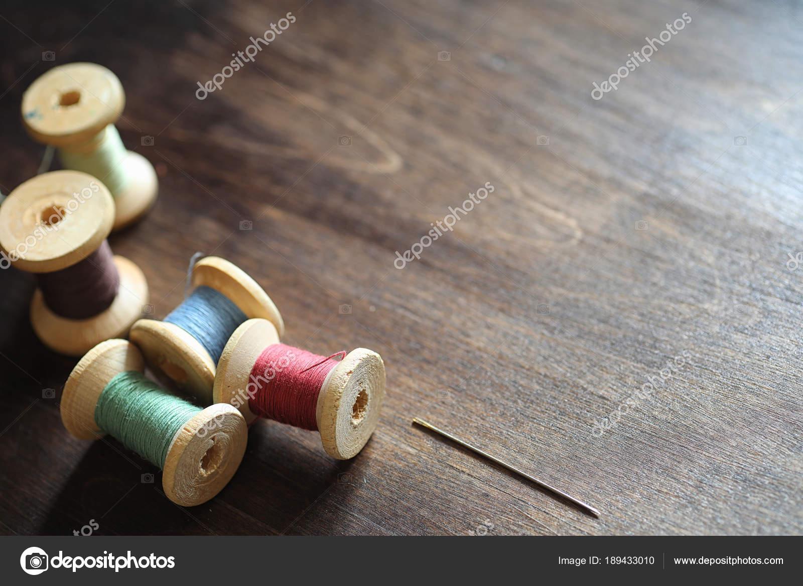 Nähgarn auf einem hölzernen Hintergrund. Gruppe von Threads auf ...